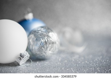 Blue, silver and white xmas ornaments on glitter holiday background. Merry christmas card. Winter holidays. Xmas theme. Happy New Year.