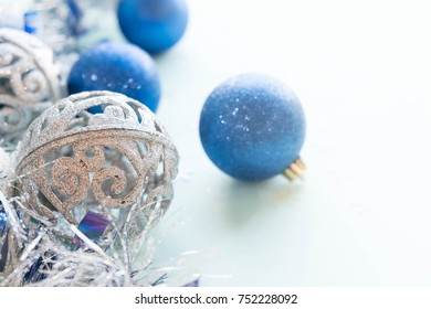 Blue and silver xmas ornaments on bright holiday background with space for text. Merry christmas!