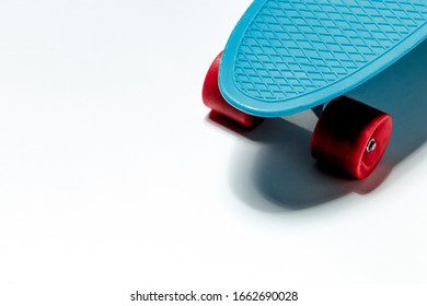 Blue skateboard cruiser with red wheels on white background with copy-space