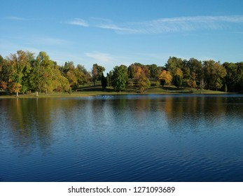 Blue skies, a few clouds, and early Autumn foliage are reflected in the calm, clear water of a lake in Kentucky.