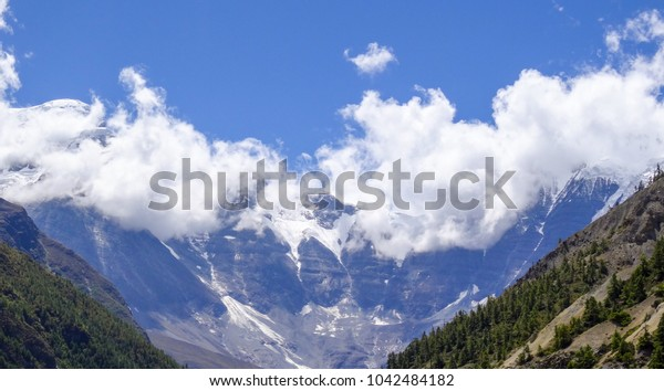 blue skies, fluffy clouds and a dark curved mountain