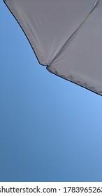 Blue skies at a Lake Michigan beach from under a beach umbrella