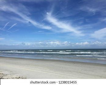Blue skies over calm waves midday in New Smyrna Beach, Florida