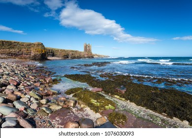 Blue skies over the ruins of Keiss Castle perched precariously on cliffs at Caithness on the north east coast of Scotland
