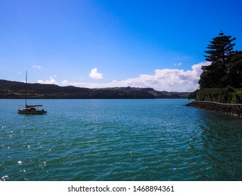 Blue skies, blue water and a boat on an autumn day at Raglan in the Waikato Region of New Zealand