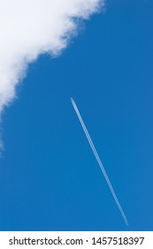 blue sky and airplane with contrail - vertical shot