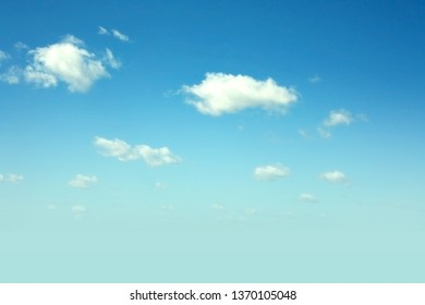 Blue sky background with clounds floating in soft blurry. Of free space for your texts and branding.
