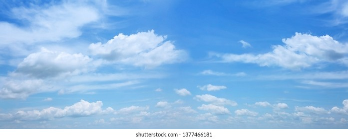 Blue sky background with clounds floating in soft blurry. Wide screen shot, Of free space for your texts and branding.