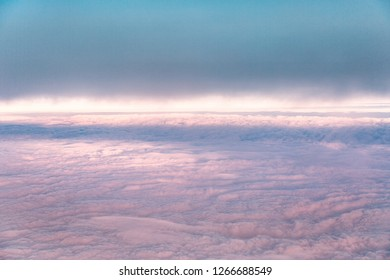 Blue sky background with pink homogeneous clouds.