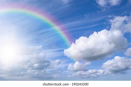 Blue sky background with rainbow and bright sun