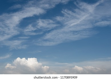 Blue sky background with white fluffy clouds.