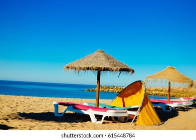 Blue sky and beach umbrella chair on beautiful tropical ocean coastline, sunny outdoors scenic background