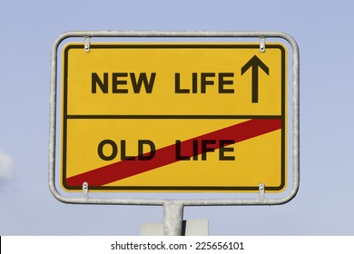 Blue sky behind a yellow city limit or place name sign informing with an arrow that you are on the way to NEW LIFE and leaving OLD LIFE