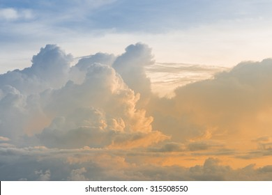 blue sky with a big cloud coating with orange sunset light