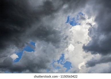 Blue sky and bright white clouds are seen above and beyond darker, stormy clouds below.