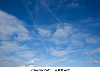 Blue sky with clouds and aircraft vapour trails