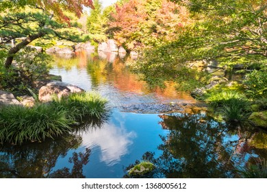 Blue sky with clouds and autumn colors from the trees reflected in the lake at Koko-en Garden, a classical Edo style Japanese Garden in Himeji, Japan.