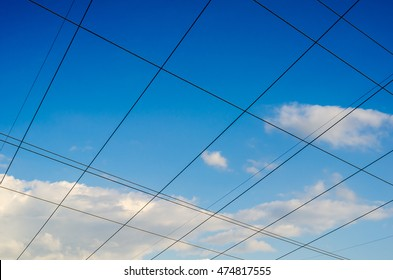 Blue sky clouds with crossing electric wire grid lines
