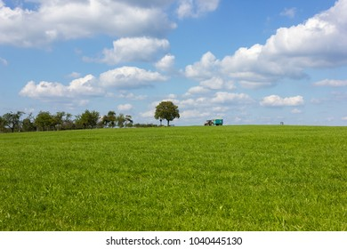 blue sky with clouds and green field and tractor on horizon in south germany rural countryside