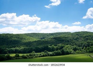 Blue sky and clouds. Mountains with trees and green meadows.