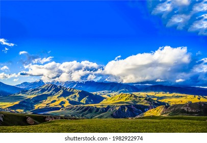 Blue sky with clouds over a hilly mountain valley. Mountain hill valley panorama. Mountain hills landscape - Shutterstock ID 1982922974