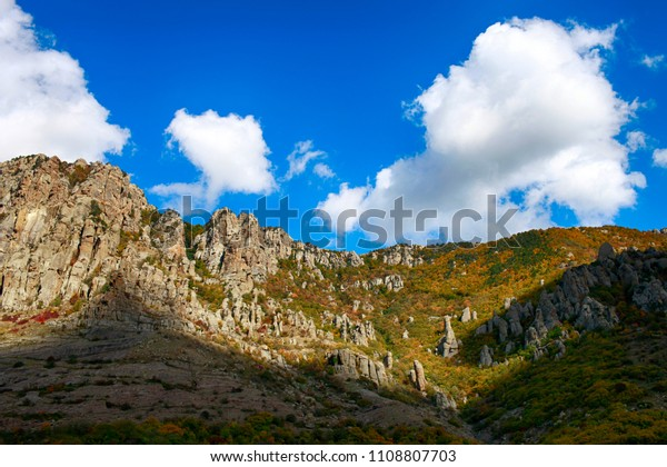 The blue sky and clouds over the mountains of Demerdzhi in the autumn in the Crimea