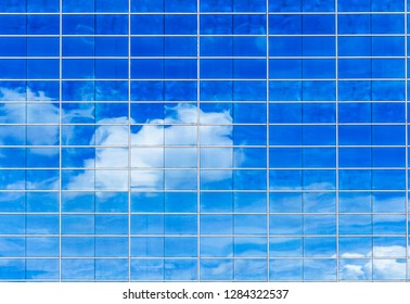 Blue sky and clouds reflected in modern office building windows