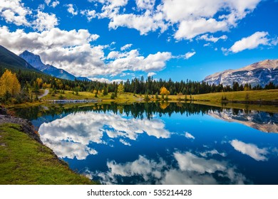 Blue sky and clouds reflected in smooth water of the lake. Shining day in the Canadian Rockies. Canmore, near Banff. Concept hiking