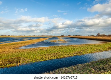Blue sky with clouds reflected in the water of a flooded part of a Dutch polder. It is at the end of a sunny and windy day in the Zonzeelse Polder,  Wagenberg, North Brabant.