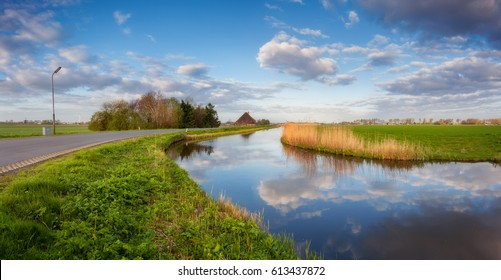 Blue sky with clouds reflected in water, road, houses near the canal, trees, green grass and yellow reeds at sunrise in Netherlands. Amazing colorful rustic landscape in Holland in spring. Nature