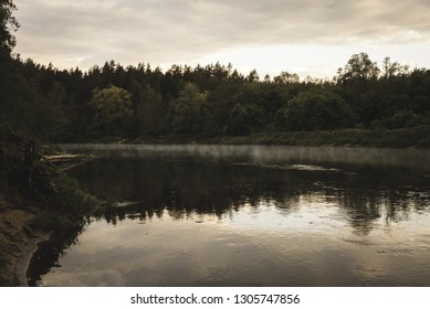blue sky and clouds reflecting in calm water of river Gauja in latvia in autumn. walk on the shore of riverbank. clear fall day. wide angle view - vintage retro look