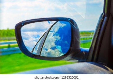 Blue sky with clouds in the sideview mirror of a car, on road countryside. Travel natural advanture concept