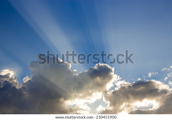 blue sky with clouds and sunbeam