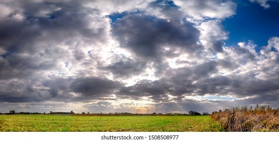 Blue sky with clouds and sunbeams. Variable, windy weather. Beautiful, colorful fields at the end of September near Wroclaw, Poland.