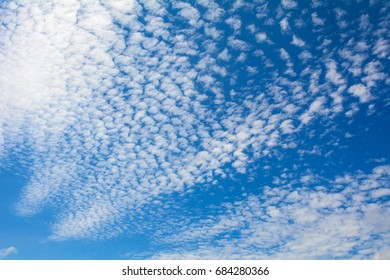 Blue sky with clouds at sunny day, for backgrounds or textures.