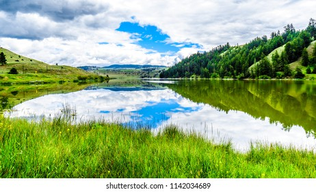 Blue Sky, Clouds and surrounding Mountains reflecting on the smooth water surface of Trapp Lake, located along Highway 5A between Kamloops and Merritt in British Columbia, Canada