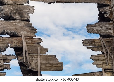 Blue sky with clouds through a ruined wooden wall