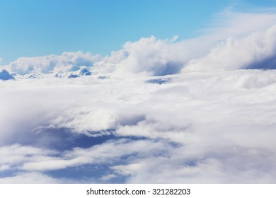 A blue sky cloudscape background with beautiful white clouds shoted from airplane