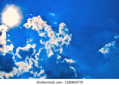 Blue sky with dazzling sun illuminating white clouds from behind