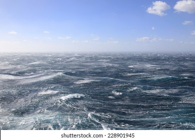 With Blue sky Fierce winds whip up the sea