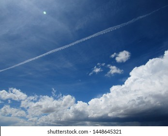 blue sky is filled with puffy, summertime cumulus clouds, as well as wispy cirrus clouds and airplane contrails. The sky and clouds combine to paint the sky.