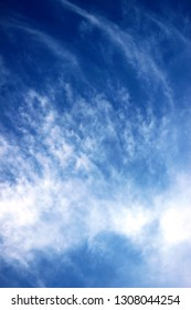 Blue sky and fine thin wispy white clouds background on a hot summer's day.