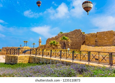 In the blue sky flies a colorful picturesque balloons. Ruins of the ancient city of Caesarea. Spring day in Israel. Lilac wildflowers on the seashore. Concept of archeological and historical tourism
