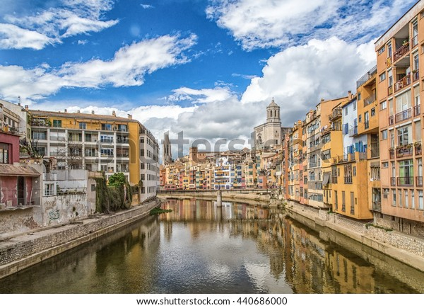 Blue sky and fluffy clouds over River Onyar in Girona, Spain