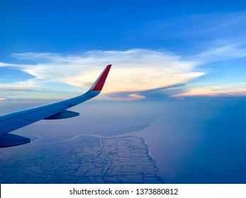 Blue sky and golden white clouds photographed in the passenger plane.