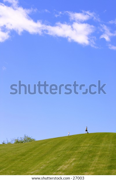 Blue sky and green hill with two small figures