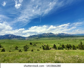 Blue sky, green meadow, and foothills in Boulder, Colorado