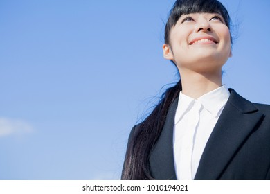 Blue sky and a Japanese business woman