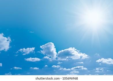 Blue sky light clouds and a bright Sun