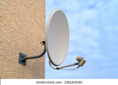 blue sky on its background white old satellite dish on a multi-storey building, television for the subscriber